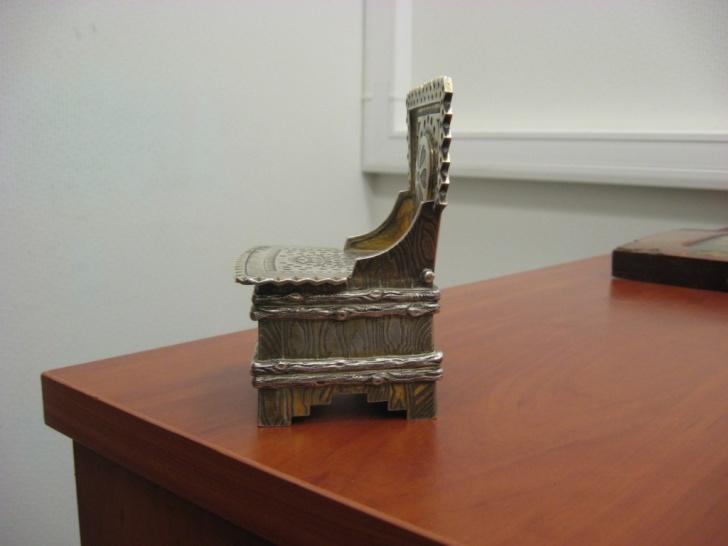 Солонка в виде стула из металла белого цвета, возможно серебро, с пробой 84 и клеймом мастераА.М. 1857 года;