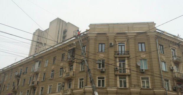 В центре Харькова альпинисты убирают ледяные глыбы с крыш домов