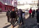 """В Харькове у активиста люди с шевронами полиции пытались забрать плакат """"Хто замовив Катю Гандзюк?"""""""
